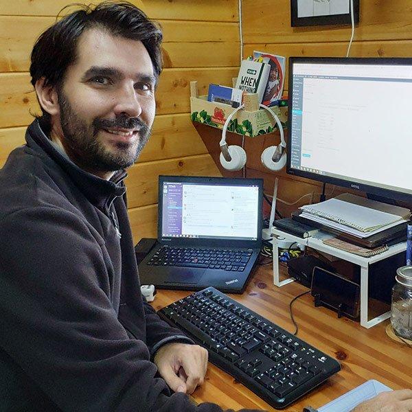 Oscar sonriente sentado frente a su ordenador